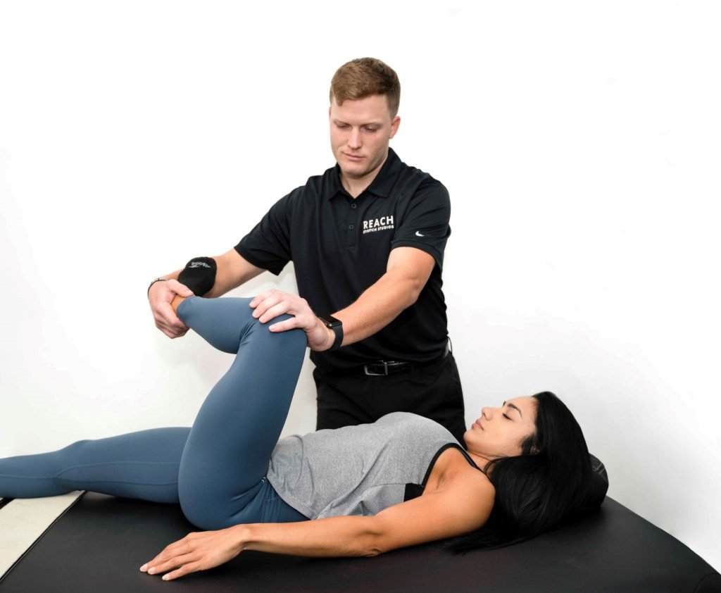 Reach Stretch & Recovery therapist assisting a member stretch and improve range of motion in their left leg.